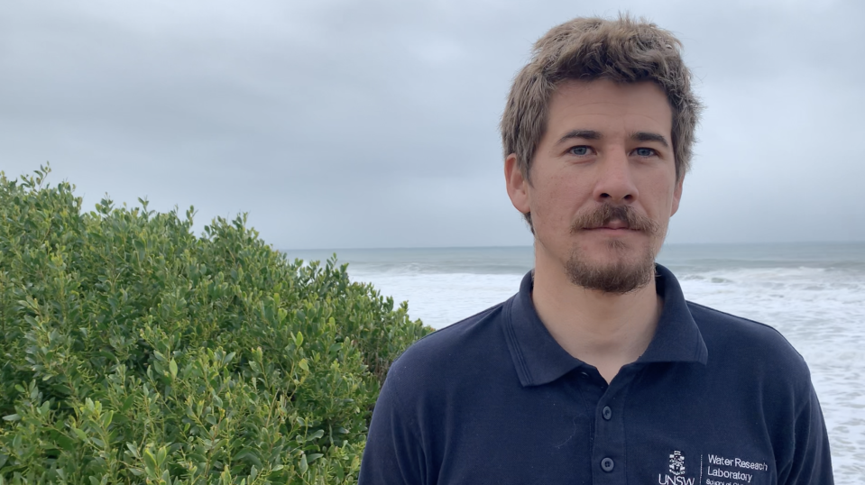 Pictured is Chris Drummond, from UNSW's Water Research Laboratory, in front of the ocean.