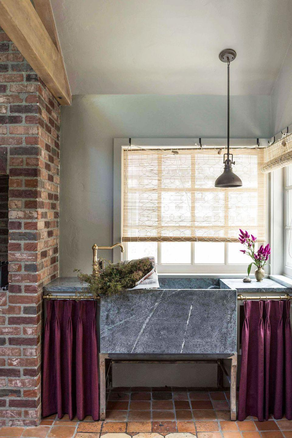 <p>In this rustic kitchen, Reath Design added short, pinch-pleat curtains around the sink to conceal cleaning supplies—and add a pop of color. </p>