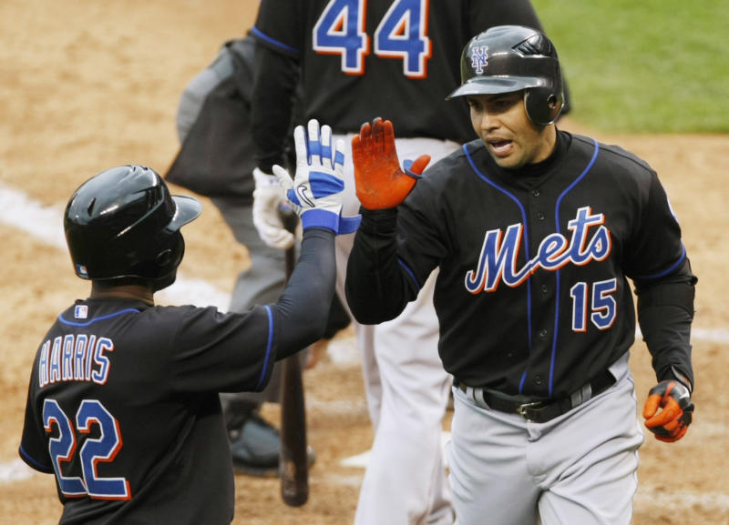 New York Mets batter Carlos Beltran (R) is congratulated by teammate Willie Harris (22) after Beltran scored his second home run of the day, a two-run homer, against the Colorado Rockies in the seventh inning of their MLB National League baseball game in Denver May 12, 2011. REUTERS/Rick Wilking (UNITED STATES - Tags: SPORT BASEBALL)