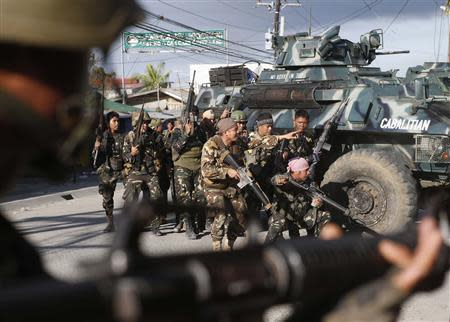 Government soldiers take cover on armoured vehicles as they try to assault positions of Muslim rebels from MNLF, during gunbattle in Zamboanga