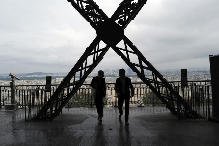 French visitors walk on the second level during the opening up of the third level and top floor of the Eiffel Tower, Wednesday, July 15, 2020 in Paris. The top floor of Paris' Eiffel Tower reopened today as the 19th century iron monument re-opened its first two floors on June 26 following its longest closure since World War II. (AP Photo/Francois Mori)