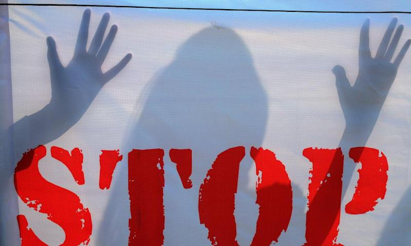The shadow of an an Indian school student falls on a banner during an awareness campaign to stop child sexual abuse in Hyderabad.