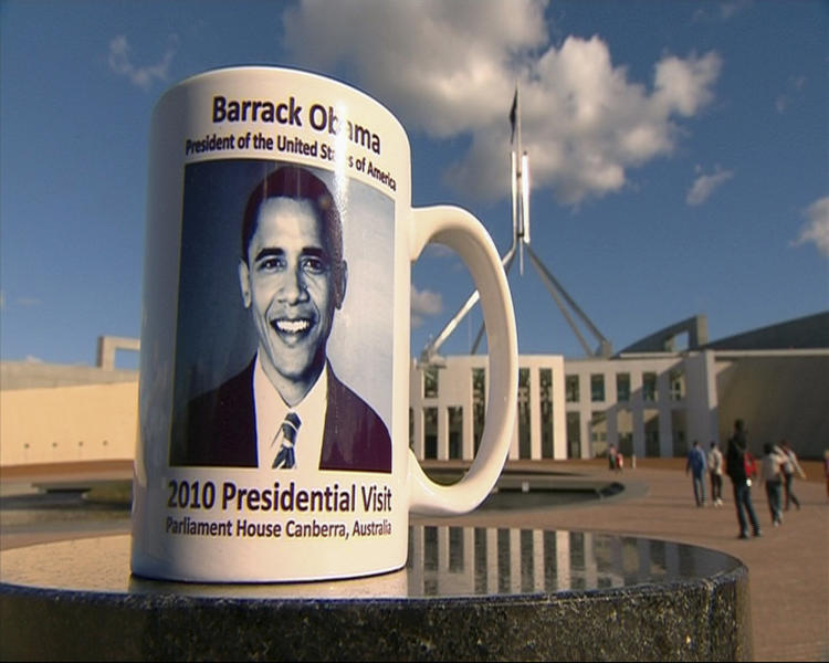 """This June 7, 2010 image from television supplied by Network 10 shows a commemorative coffee mug of the 2010 presidential visit by Barack Obama sitting on a stone pillar in front of Parliament House in Canberra, Australia. A Parliament House official told senators on Monday, May 21, 2012 that 198 mugs were smashed and buried under wet concrete at a loading dock behind the building. One senator called it a """"mafia-style execution"""" for the mugs, which had an extra """"r"""" printed in Obama's first name. (AP Photo/Network 10) AUSTRALIA OUT"""