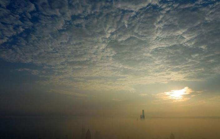 The sun rises over the financial district of Pudong on a polluted day in Shanghai in September 2018.
