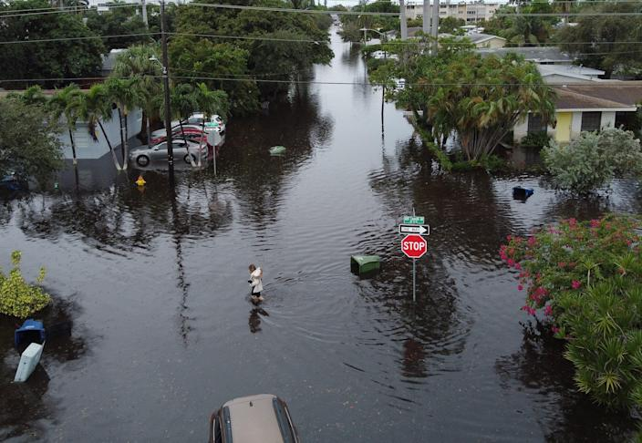 An aerial view from a drone shows a woman crossing a street inundated with floodwater on Dec. 23, 2019, in Hallandale, Fla. Hallandale is in Broward County, which has the highest of any county in the country.