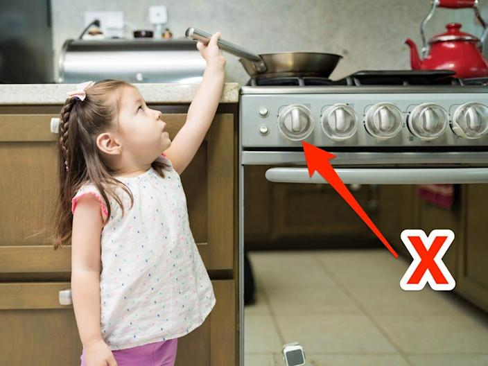 A child reaches for the pan on the stove.