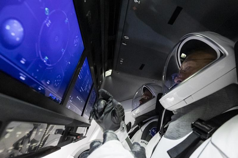 Testing the touchscreen control dashboard of the Crew Dragon with their high-tech smart gloves (SpaceX)