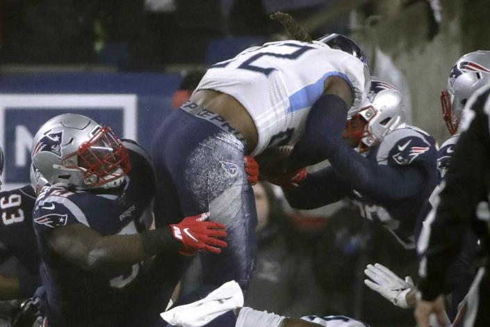 Tennessee Titans running back Derrick Henry goes over New England Patriots defenders for a touchdown in the first half of an NFL wild-card playoff football game, Saturday, Jan. 4, 2020, in Foxborough, Mass. (AP Photo/Elise Amendola)