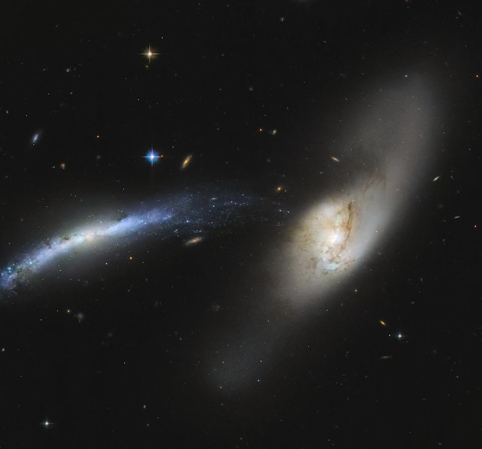 "Galaxy NGC 2799 (on the left) and galaxy NGC 2798 (on the right) form a ""galactic waterfall,"" which stands out in this image snapped by the Hubble Space Telescope. These are interacting galaxies, which influence each other and may eventually even merge."