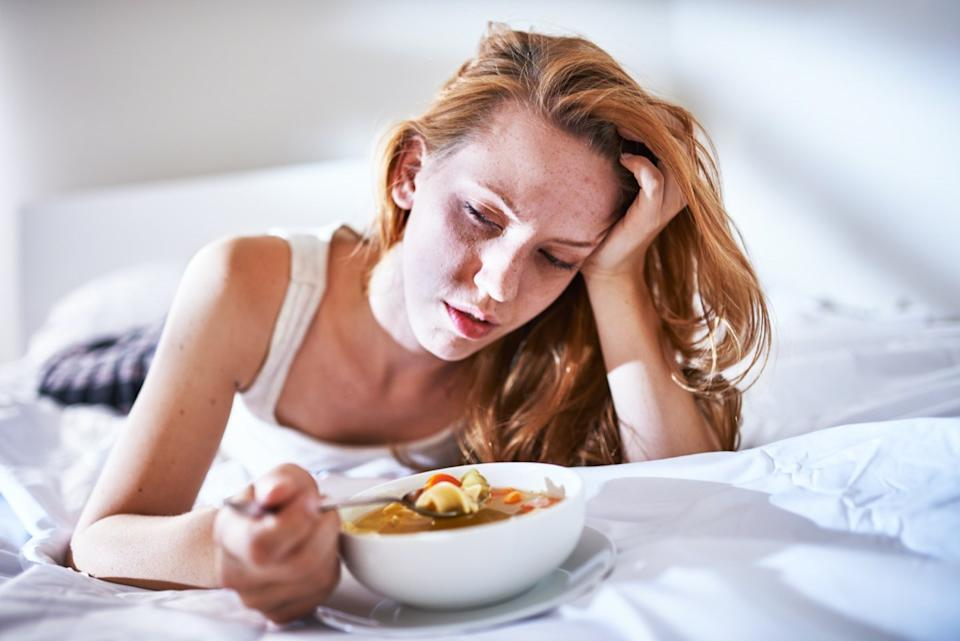 Sick woman eating soup in bed.