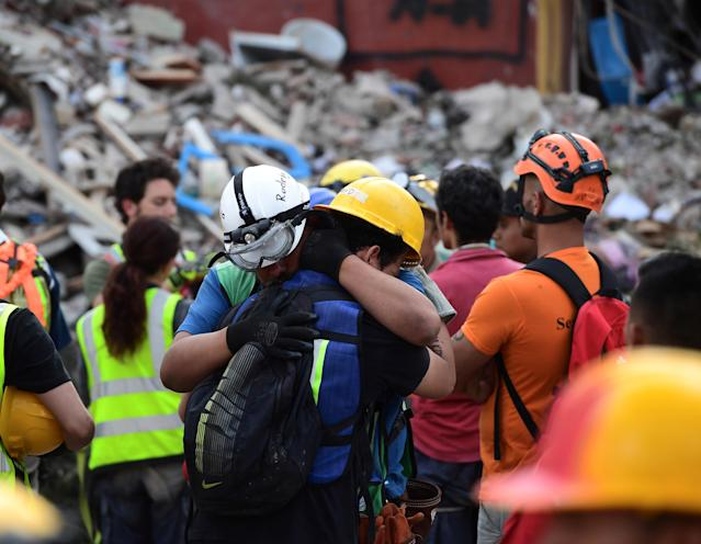 <p>Rescue workers embrace each other after a seismic alert sounded in Mexico City on Sept. 23, 2017, four days after the powerful quake that hit central Mexico. (Photo: Ronaldo Schemidt/AFP/Getty Images) </p>