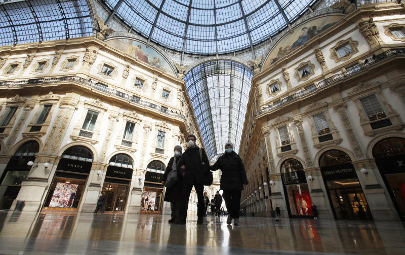 People wear masks as they walks inside Vittorio Emanuele II gallery, in downtown Milan, Italy, Sunday, March 8, 2020. Italy announced a sweeping quarantine early Sunday for its northern regions, igniting travel chaos as it restricted the movements of a quarter of its population in a bid to halt the new coronavirus' relentless march across Europe. (AP Photo/Antonio Calanni)