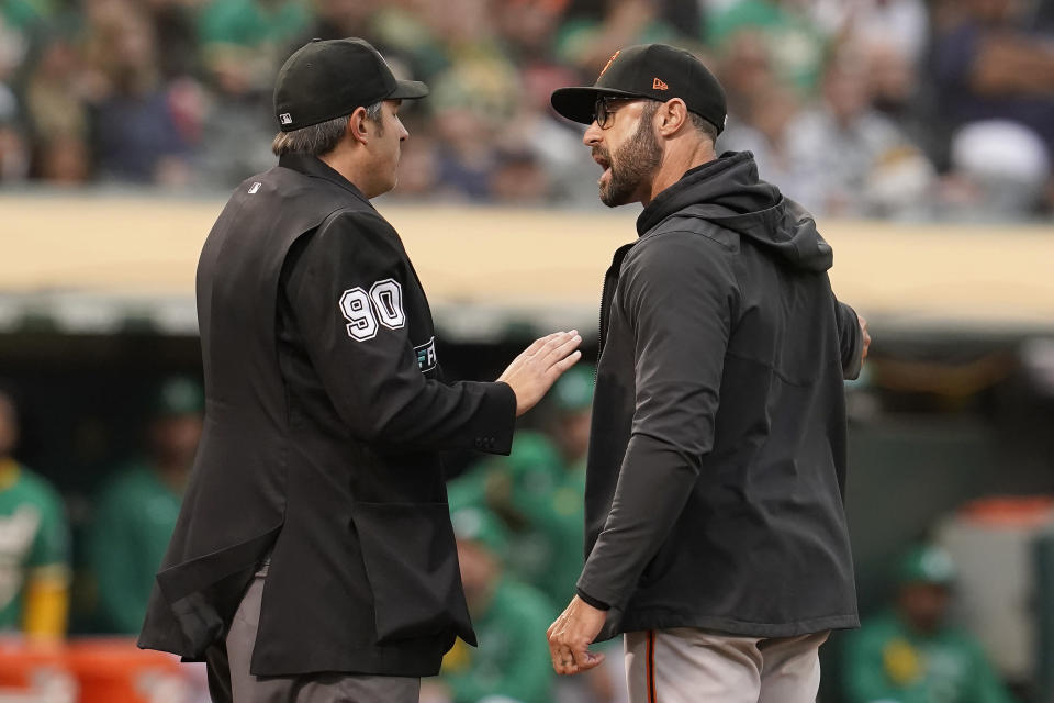 San Francisco Giants manager Gabe Kapler, right, gestures while talking with umpire Mark Ripperger (90) during the second inning of a baseball game against the Oakland Athletics in Oakland, Calif., Friday, Aug. 20, 2021. (AP Photo/Jeff Chiu)