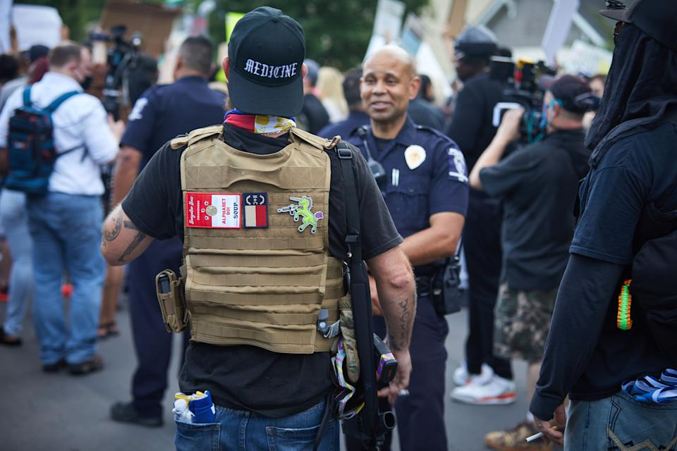 A member of the far-right militia, Boogaloo Bois, walks next to protestors demonstrating outside Charlotte Mecklenburg Police Department Metro Division 2, just outside of downtown Charlotte, North Carolina, on May 29, 2020. The protest was sparked by protests in Minneapolis, over the death of George Floyd, a black man who died after a white policeman kneeled on his neck for several minutes. (Logan Cyrus / AFP via Getty Images)