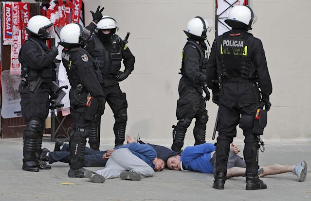 Police guard handcuffed men after they arrested them prior to the Euro 2012 soccer championship Group A match between Poland and Russia in Warsaw, Poland, Tuesday, June 12, 2012. Russian soccer fans clashed with police and Poland supporters in separate incidents in Warsaw on Tuesday, just hours before the two teams were to meet in an emotionally charged European Championship match. Several people were injured. (AP Photo/Gero Breloer)