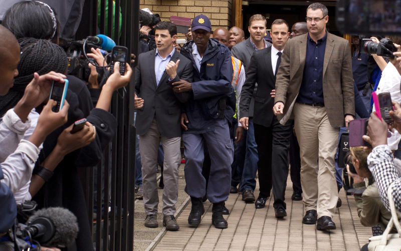 Oscar Pistorius, center, walks out of the high court in Pretoria, South Africa, Friday, March 14, 2014. Pistorius is charged with murder for the shooting death of his girlfriend, Reeva Steenkamp, on Valentines Day in 2013. (AP Photo/Themba Hadebe)