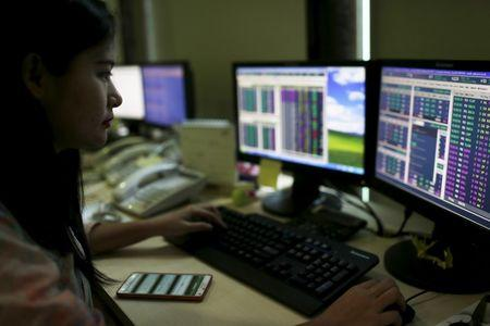 A trader monitors share prices at the Bank Mandiri Sekuritas trading floor in Jakarta August 25, 2015. REUTERS/Beawiharta/Files