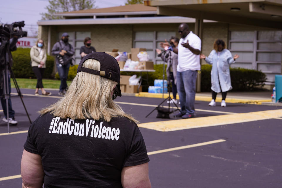 A women wears a shirt calling for the end of gun violence during a vigil at the Olivet Missionary Baptist Church for the victims of the shooting at a FedEx facility in Indianapolis, Saturday, April 17, 2021. A gunman killed eight people and wounded several others before taking his own life in a late-night attack at a FedEx facility near the Indianapolis airport, police said. (AP Photo/Michael Conroy)