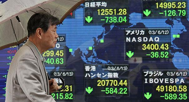 A pedestrian walks past an electronic stock board in Tokyo, Japan, on Thursday, June 13, 2013. Photographer: Junko Kimura/Bloomberg