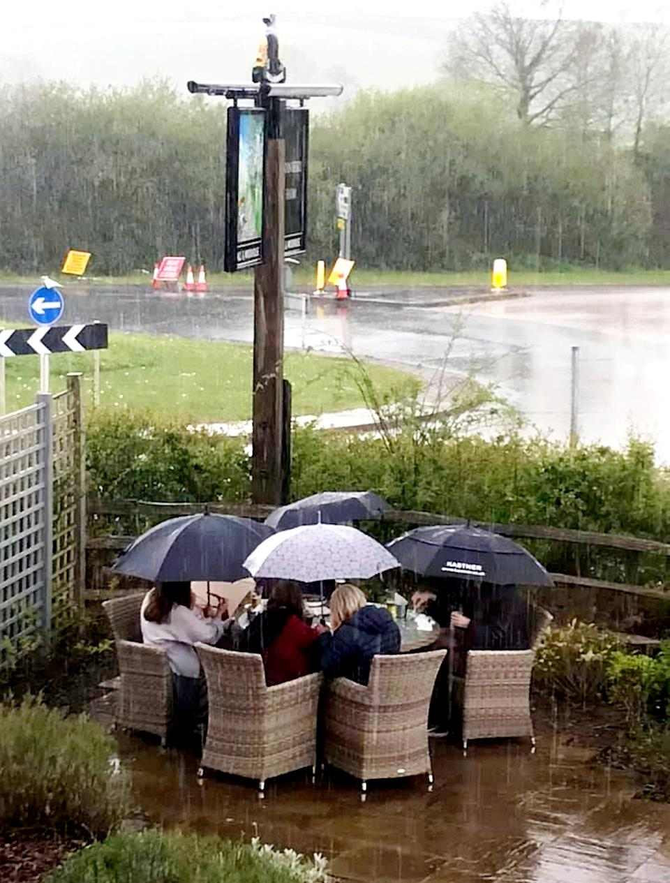 The comical photo showed the family huddled under umbrellas in a beer garden as they tried to enjoy the Bank Holiday. (SWNS)
