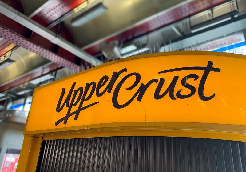 A logo is pictured above a closed-down and shuttered Upper Crust food outlet in a train station in London on July 1, 2020. Photo: DANIEL LEAL-OLIVAS/AFP via Getty Images