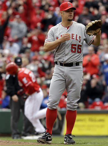 Los Angeles Angels starting pitcher Joe Blanton stands by the mound after giving up a 2-run home run to Cincinnati Reds' Chris Heisey, rounding the bases at left, during the fifth inning of an interleague baseball game, Thursday, April 4, 2013, in Cincinnati. (AP Photo/Al Behrman)