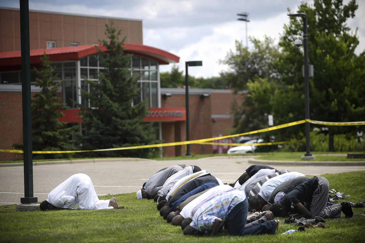 <p>Mohamed Omar, left, the executive director of the Dar Al Farooq Center Islamic Center leads afternoon prayers outside the police tape surrounding the center Saturday Aug. 5, 2017 in Bloomington, Minn. (Photo: Aaron Lavinsky/Star Tribune via AP) </p>
