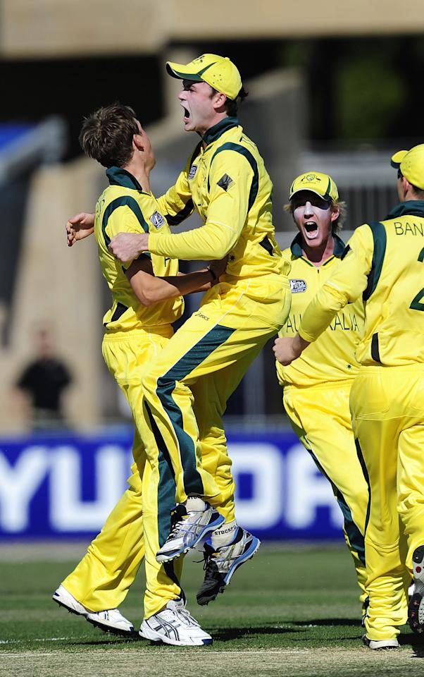 TOWNSVILLE, AUSTRALIA - AUGUST 11:  Joel Paris (L) celebrates taking the wicket of Daniel Bell-Drummond of England with team mates during the ICC U19 Cricket World Cup 2012 match between Australia and England at Tony Ireland Stadium on August 11, 2012 in Townsville, Australia.  (Photo by Ian Hitchcock-ICC/Getty Images)