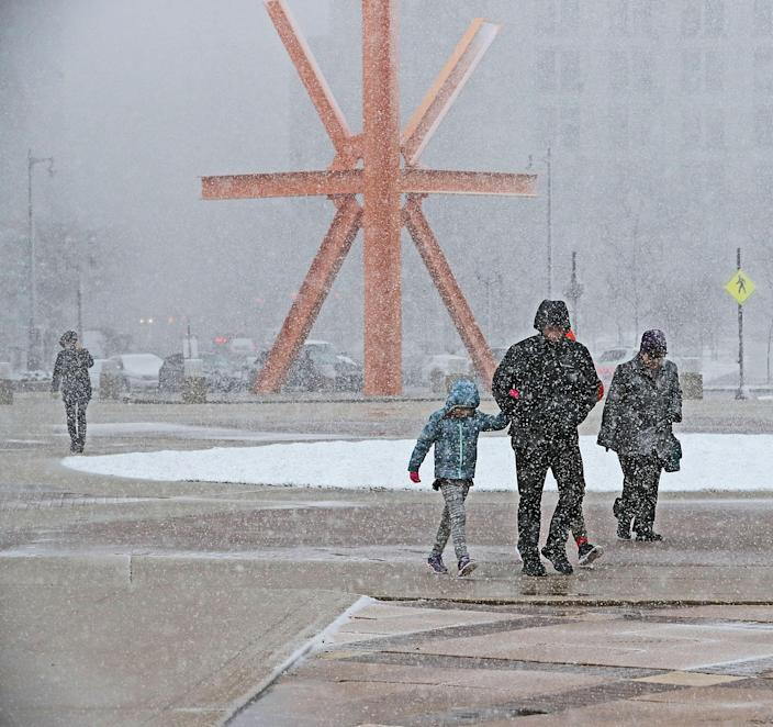 """Gusty winds and wet snow greeted visitors to Milwaukee's lakefront as they walked past the steel sculpture """"The Calling"""" by Mark di Suvero located in O'Donnell Park on April 14, 2019."""