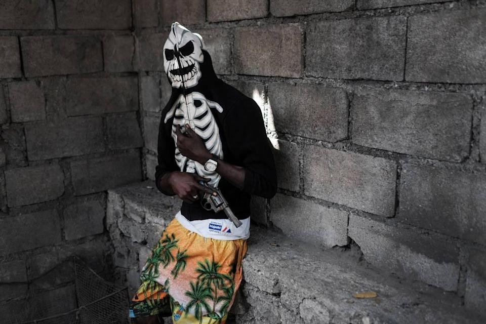 A gang member poses with his revolver before a rally to demand justice for slain Haitian President Jovenel Moïse in the La Saline neighborhood of Port-au-Prince, Haiti, Monday, July 26, 2021. As conditions have deteriorated, gangs have been driving people from their homes in the impoverished neighborhoods of Port-au-Prince.