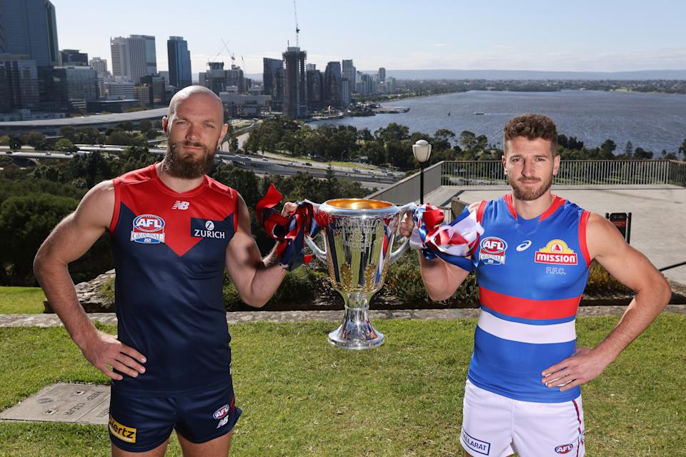 Pictured here, Demons captain Max Gawn and Bulldogs opposite Marcus Bontempelli pose with the AFL trophy.