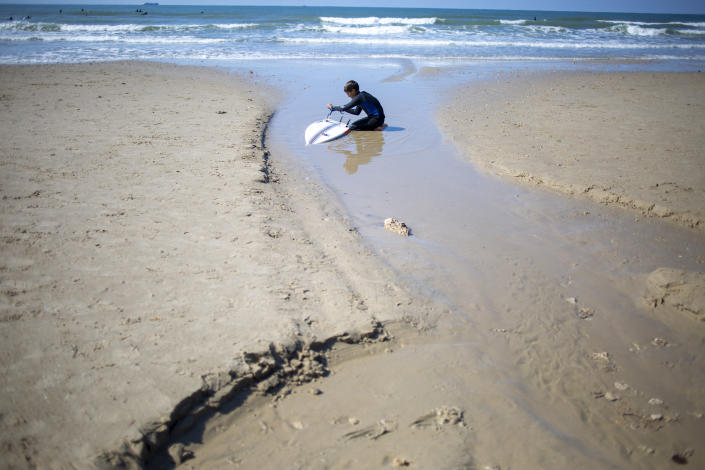 A surfer cleans his tar covered surfboard from an oil spill in the Mediterranean Sea in Gador nature reserve near Hadera, Israel, Saturday, Feb. 20, 2021. Hundreds of volunteers are taking part in a cleanup operation of Israeli shoreline as investigations are underway to determine the cause of an oil spill that threatens the beach and wildlife, at Gador Nature Reserve near the northern city of Hadera, the tar smeared fish, turtles, and other sea creatures. (AP Photo/Ariel Schalit)
