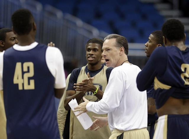 Pittsburgh head coach Jamie Dixon, center, talks with his players during practice for the NCAA college basketball tournament in Orlando, Fla., Wednesday, March 19, 2014. Colorado plays against Pittsburgh in a second round game on Thursday. (AP Photo/John Raoux)