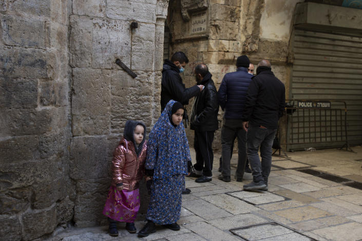 A girl wearing a head-to-toe Islamic garment stands with her sister at a police checkpoint as worshippers enter the Al Aqsa Mosque compound for Friday prayers in the Old City of Jerusalem, Friday, Jan. 22, 2021. Many people prayed outside the gates of the Old City, due to coronavirus restrictions. (AP Photo/Maya Alleruzzo)