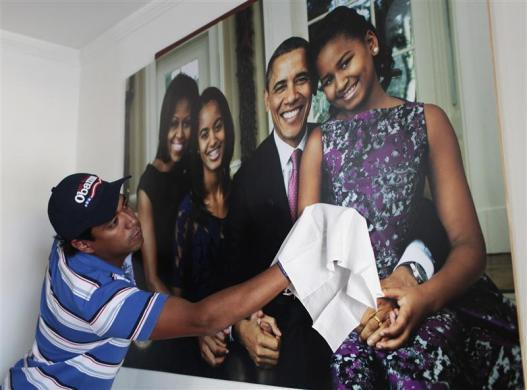 Colombian attorney Silvio Carrasquilla cleans a poster of President Obama and his family on a wall inside his home in Turbaco, near Cartagena, April 11, 2012.