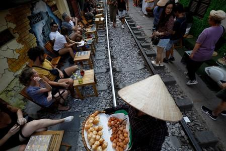 A woman sells snacks as tourists sit at tables for drinks along the railway at the Old Quarter in Hanoi, Vietnam