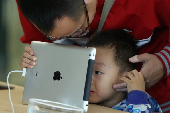 BEIJING, CHINA - OCTOBER 20: A Chinese customer and his son look at the iPad in the newly opened Apple Store in Wangfujing shopping district on October 20, 2012 in Beijing, China. Apple Inc. opened its sixth retail store on the Chinese mainland Saturday. The new Wangfujing store is Apple's largest retail store in Asia.  (Photo by Feng Li/Getty Images)