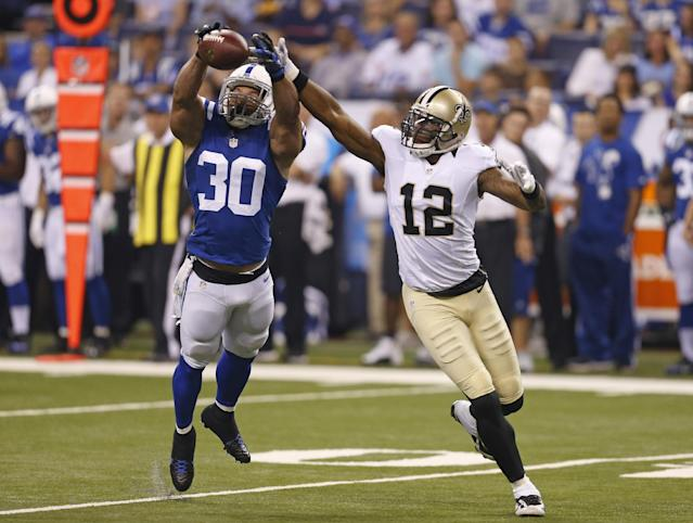 Indianapolis Colts strong safety LaRon Landry , left, breaks up a pass indented for New Orleans Saints wide receiver Marques Colston during the first half of an NFL preseason football game in Indianapolis, Saturday, Aug. 23, 2014. (AP Photo/Sam Riche)