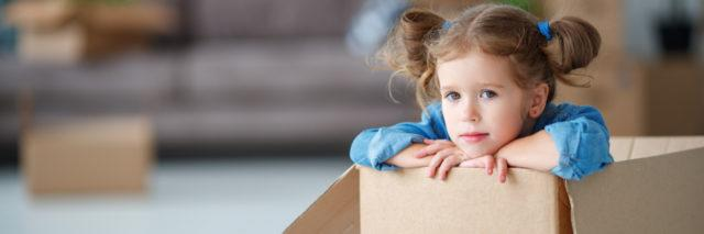 young girl in pigtails sitting inside a cardboard box getting ready to move into a new house