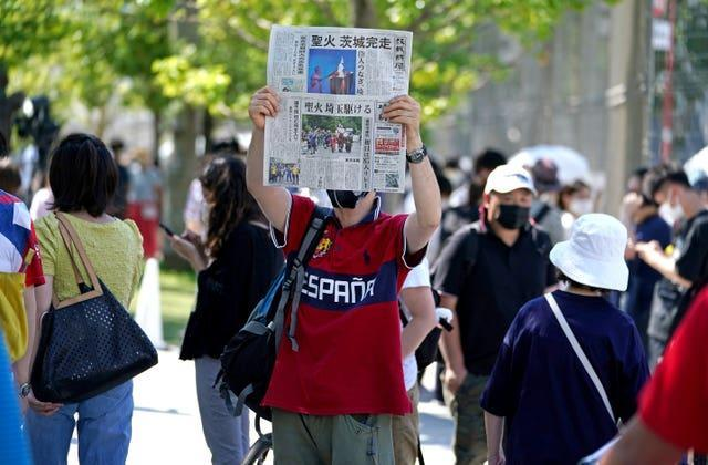 A newspaper is held up in protest outside the Olympic Stadium