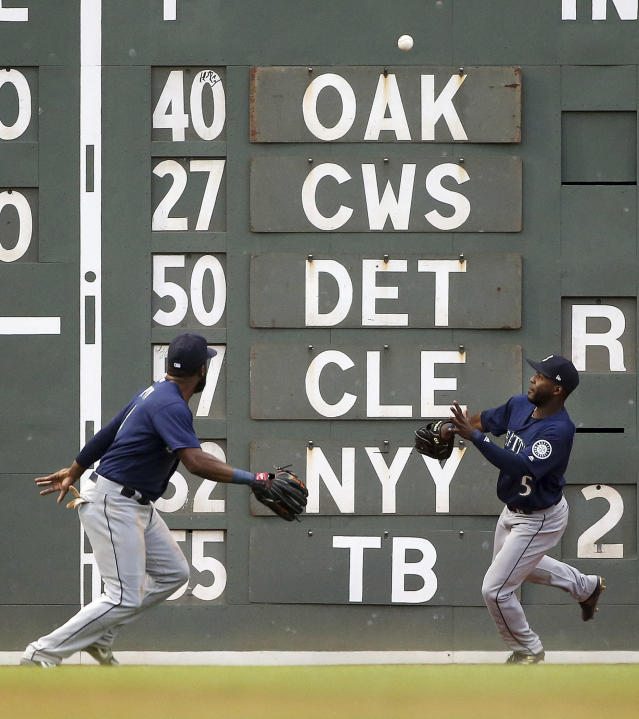 Seattle Mariners left fielder Denard Span, left, fields a double off the wall by Boston Red Sox's J.D. Martinez, as center fielder Guillermo Heredia (5) also chases the ball during the second inning of a baseball game at Fenway Park, Friday, June 22, 2018, in Boston. (AP Photo/Elise Amendola)