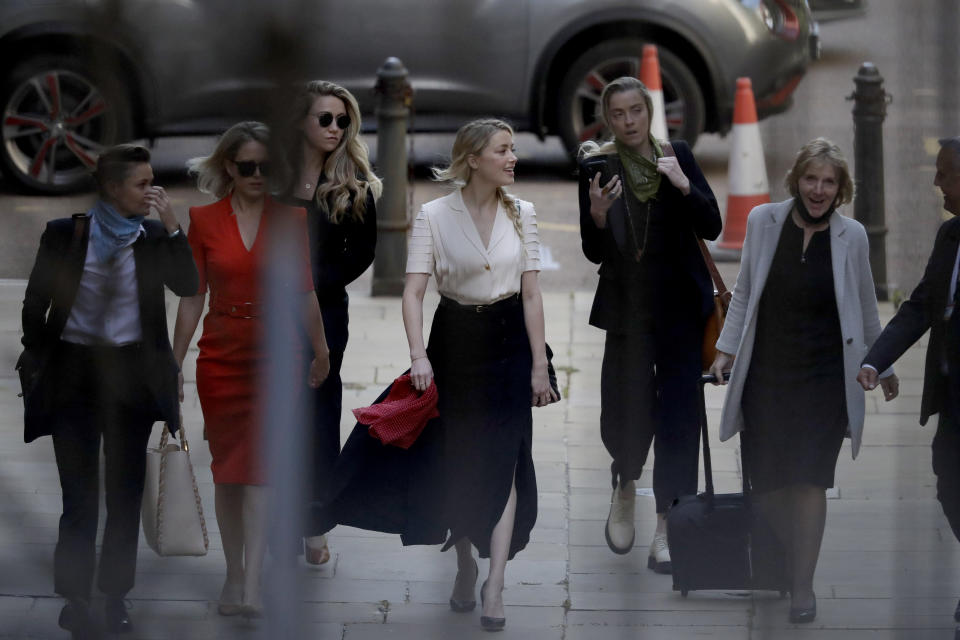 Actress Amber Heard, center, arrives at the High Court in London, Monday, July 20, 2020. Amber Heard started Monday to give evidence at the High Court in London as part of Johnny Depp's libel case against The Sun over allegations of domestic violence during the couple's relationship. (AP Photo/Matt Dunham)