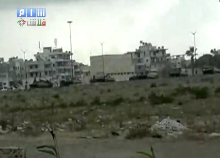 This image made from amateur video and released by Shams News Network and accessed via The Associated Press Television News on Saturday, Aug. 13, 2011, shows a long shot of military vehicles lined up on road, backdrop of buildings taking up positions near Latakia, Syria. Syrian tanks, security agents and pro-regime gunmen fanned out into the streets of two towns to root out protesters demanding the ouster of President Bashar Assad in a sweep Saturday that killed at least three people. The heaviest assault was in the Mediterranean coastal city of Latakia, where a day earlier thousands had turned out in protests. (AP Photo/Shams News Network, via APTN)  THE ASSOCIATED PRESS CANNOT INDEPENDENTLY VERIFY THE CONTENT, DATE, LOCATION OR AUTHENTICITY OF THIS MATERIAL