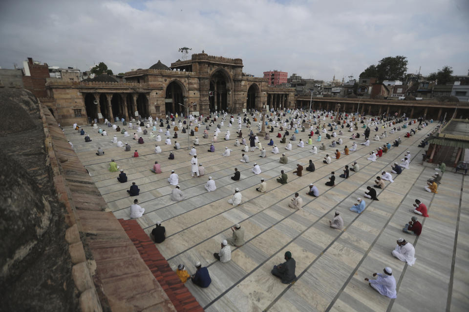 Indian Muslims sit while maintaining social distance and attend an Eid al-Adha prayer service at the Jama Masjid in Ahmedabad, India, Saturday, Aug. 1, 2020. Eid al-Adha, or the Feast of the Sacrifice, is observed by sacrificing animals to commemorate the prophet Ibrahim's faith in being willing to sacrifice his son. (AP Photo/Ajit Solanki)