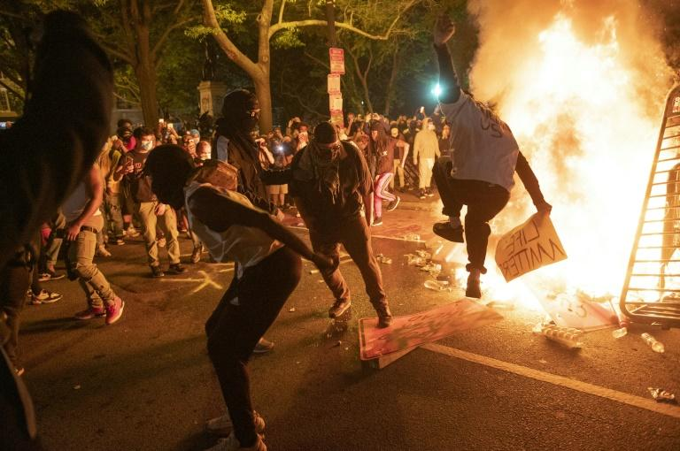 Protesters jump on a street sign near a burning barricade during a demonstration against the death of George Floyd near the White House on May 31, 2020 (AFP Photo/ROBERTO SCHMIDT)