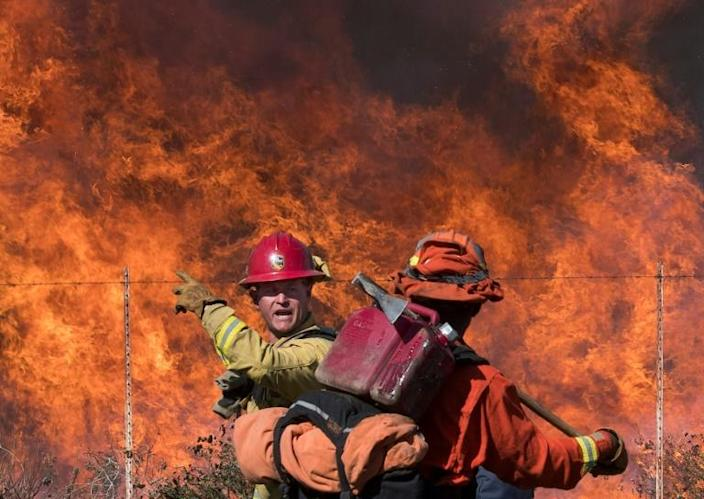 A firefighter (L) speaks to an inmate firefighter as they prepare to put out flames on the road leading to the Reagan Library during the Easy Fire in Simi Valley, California on October 30, 2019 (AFP Photo/Mark RALSTON)
