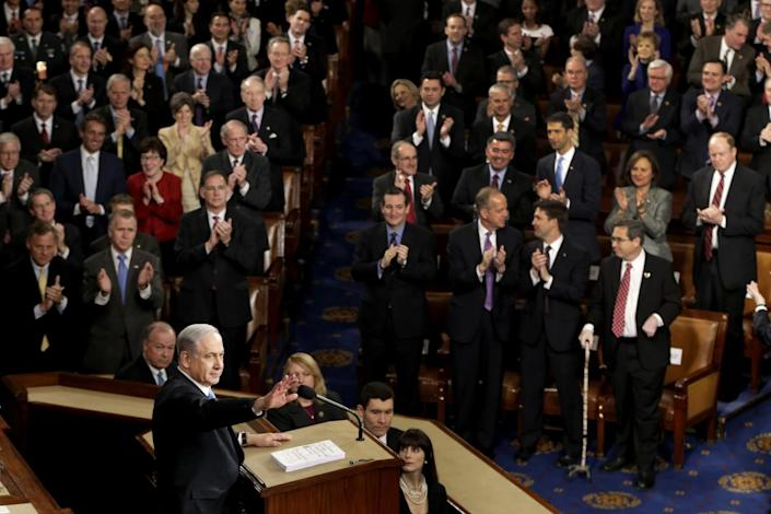 Congress members stand and applaud Benjamin Netanyahu, who stands on a podium.