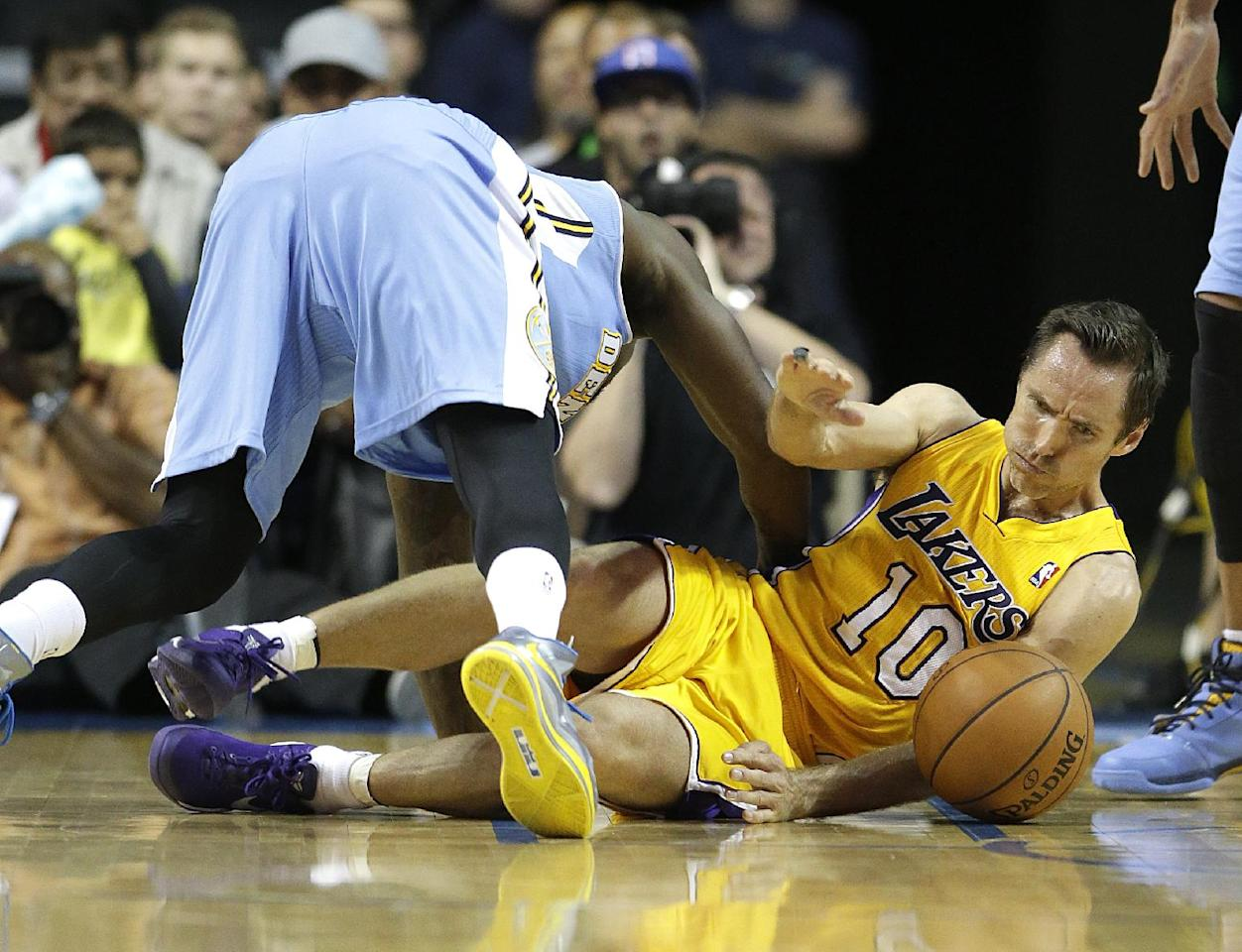 Denver Nuggets' Randy Foye, top, and Los Angeles Lakers' Steve Nash fall to the court as they fight for a loose ball in the second half of an NBA preseason basketball game on Tuesday, Oct. 8, 2013, in Ontario, Calif. The Lakers won 90-88. (AP Photo/Jae C. Hong)