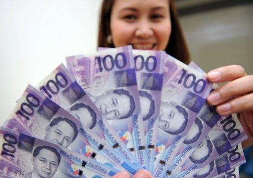 A bank employee displays 100 peso notes in Manila