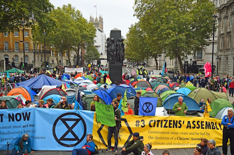 Extinction Rebellion (XR) protesters camp in tents around the Monument to the Women of World War II on Whitehall in Westminster, central London, as the climate change protest continued into a second day. (Photo by Kirsty O'Connor/PA Images via Getty Images)